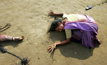 An Indian woman mourns the death of her relative (R) who was killed in tsunami on Sunday in Cuddalore, some 180 km (112 miles) south of the southern Indian city of Madras December 28, 2004. REUTERS/Arko Datta Pictures of the Month December 2004 Pictures of the Year 2004 AD/SH Year End Pictures 2004